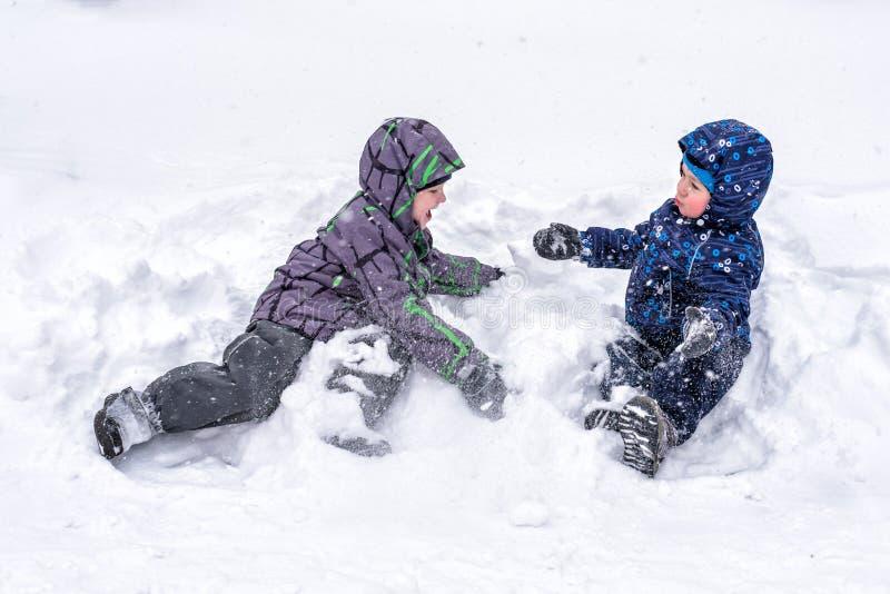 Lyckliga vänner som har gyckel med snö royaltyfri fotografi