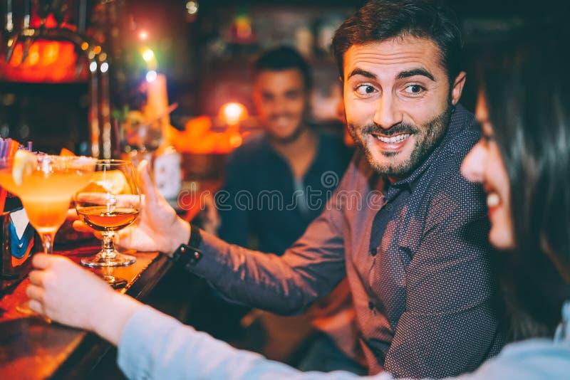 Lyckliga vänner som har gyckel på coctailstången - ungt moderiktigt folk som dricker coctailar och tillsammans skrattar i en klub arkivbilder