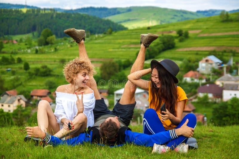Lyckliga vänner som har gyckel på kullen som tycker om rekreation och samtal som är horisontal royaltyfri fotografi