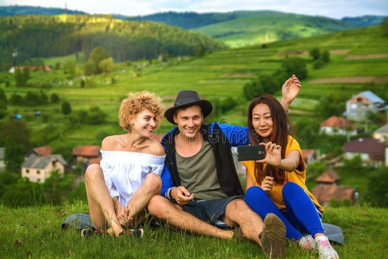 Lyckliga vänner som har gyckel på kullen som tycker om rekreation och samtal som är horisontal royaltyfri foto
