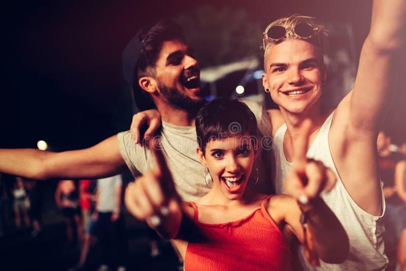 Lyckliga vänner som har gyckel på musikfestivalen royaltyfria foton