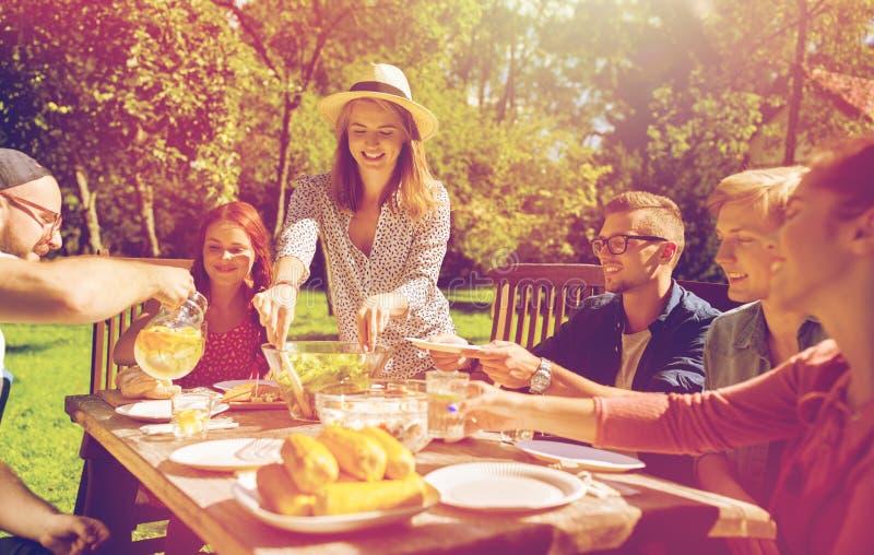 Lyckliga vänner som har matställen på det trädgårds- partiet för sommar royaltyfria bilder