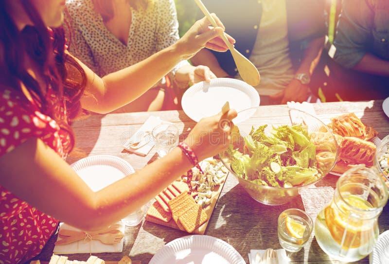 Lyckliga vänner som har matställen på sommarpartiet arkivbild