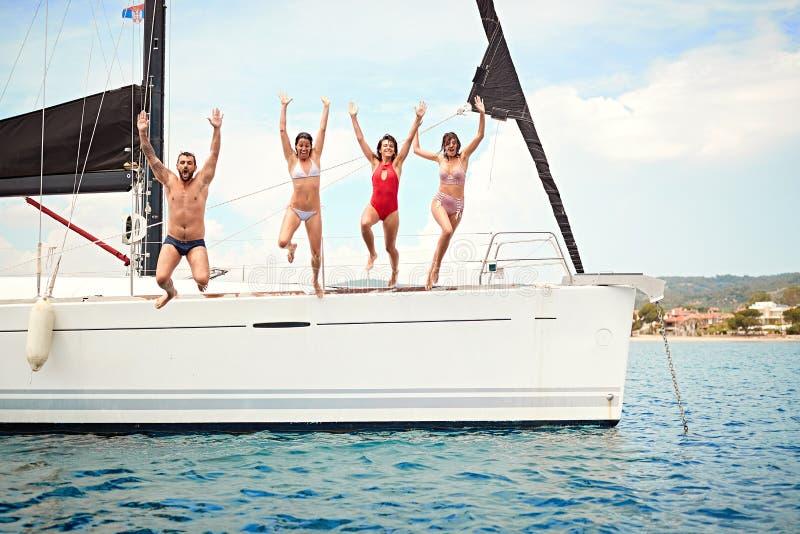 Lyckliga vänner som hoppar från segelbåten i havet royaltyfri bild