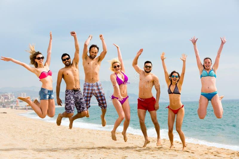 Lyckliga vänner som hoppar på stranden royaltyfri foto