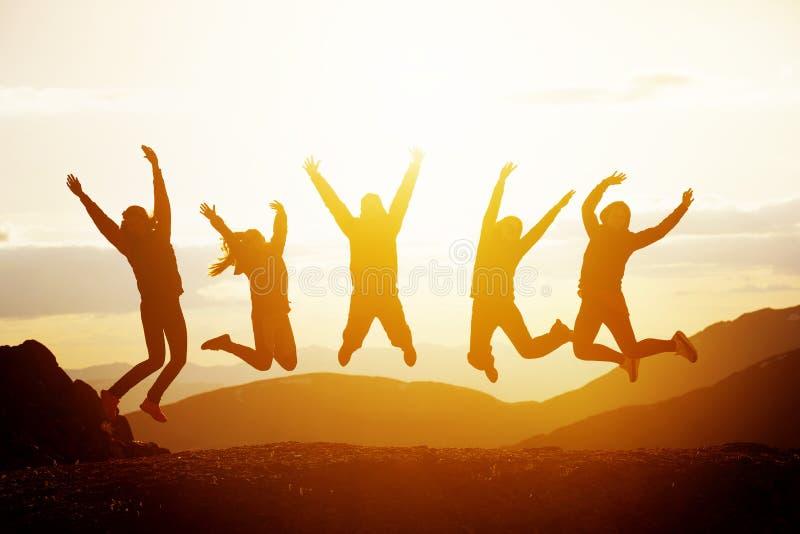 Lyckliga vänner som hoppar solnedgångberg royaltyfri fotografi