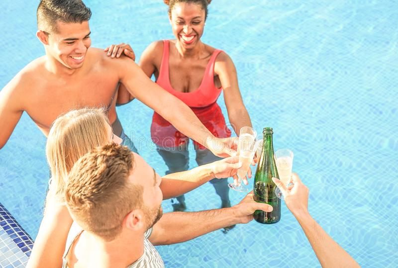 Lyckliga vänner som hurrar med champagne i pölen - ungdomarsom har gyckel som gör ett parti och rostar exponeringsglas av prosecc royaltyfri fotografi