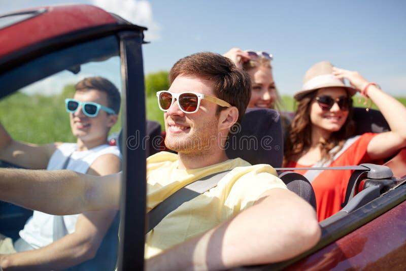 Lyckliga vänner som kör i cabrioletbil royaltyfria foton