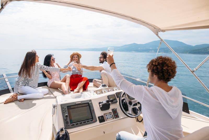 Lyckliga vänner som klirrar exponeringsglas av champagne och seglar på yachten royaltyfria bilder