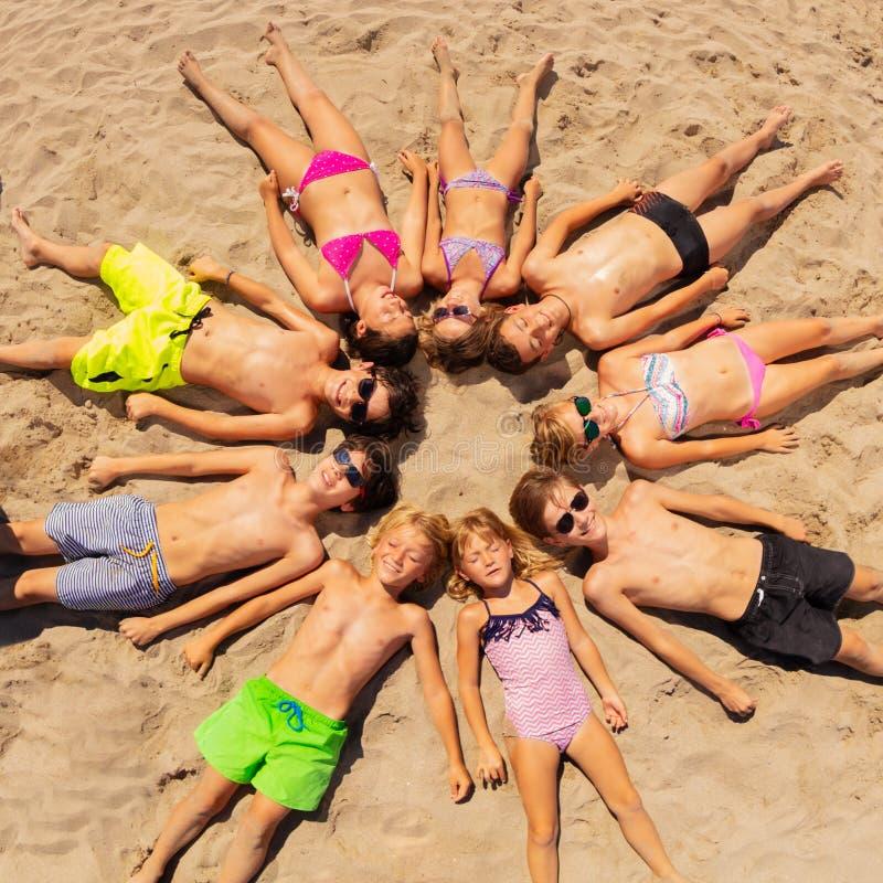 Lyckliga vänner som lägger på stranden som bildar en cirkel royaltyfria bilder
