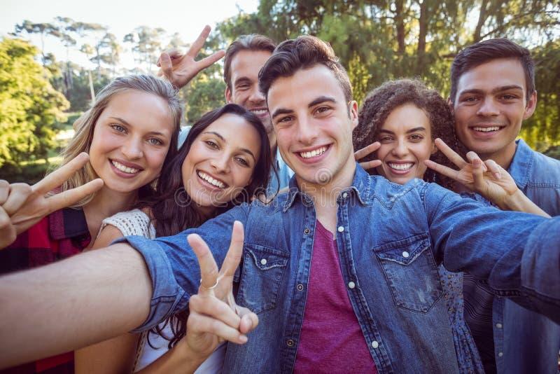 Lyckliga vänner som ler på kameran fotografering för bildbyråer