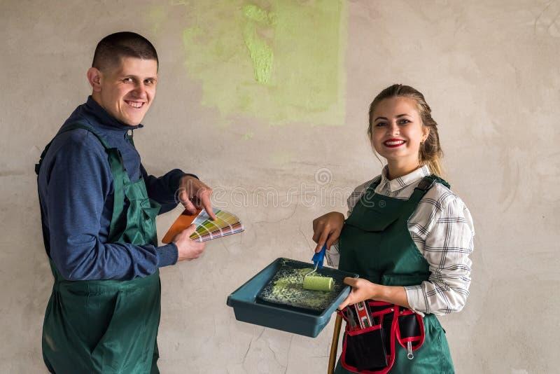 Lyckliga vänner som målar väggar i grön färg royaltyfri bild