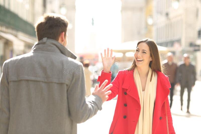 Lyckliga vänner som möter och hälsar i gatan fotografering för bildbyråer