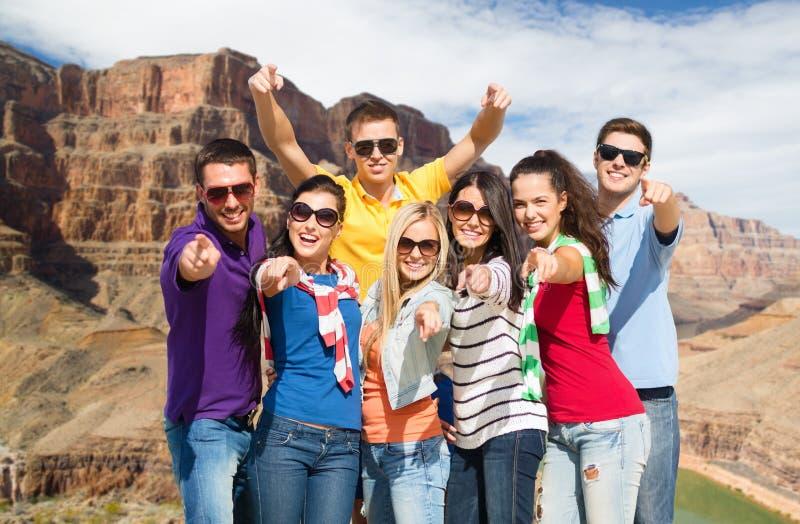 Lyckliga vänner som pekar på dig över Grandet Canyon royaltyfri foto