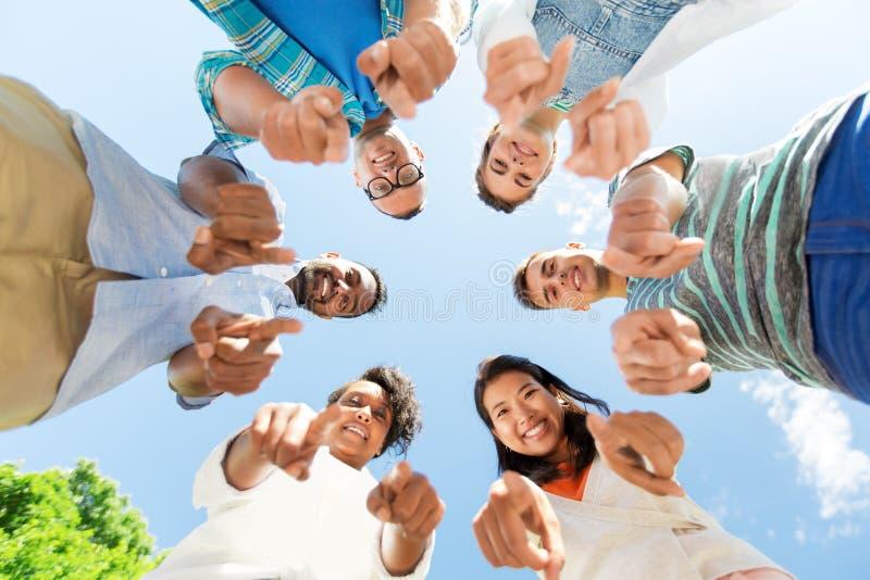 Lyckliga vänner som pekar på dig som står i cirkel royaltyfri fotografi