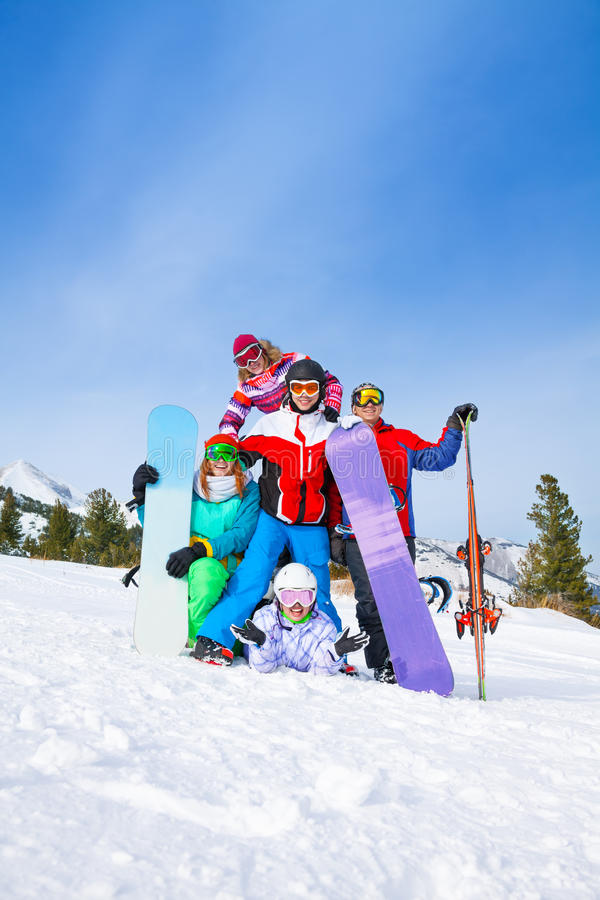 Lyckliga vänner som poserar med snowboards och, skidar arkivfoto