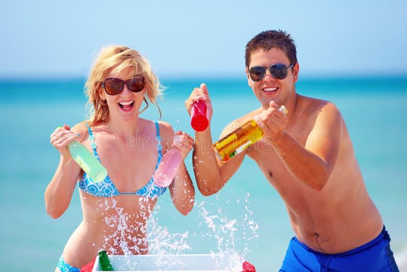 Lyckliga vänner som rymmer att kyla, dricker på stranden royaltyfri foto
