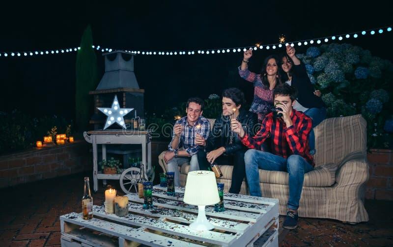 Lyckliga vänner som rymmer tomtebloss i ett nattparti arkivbild
