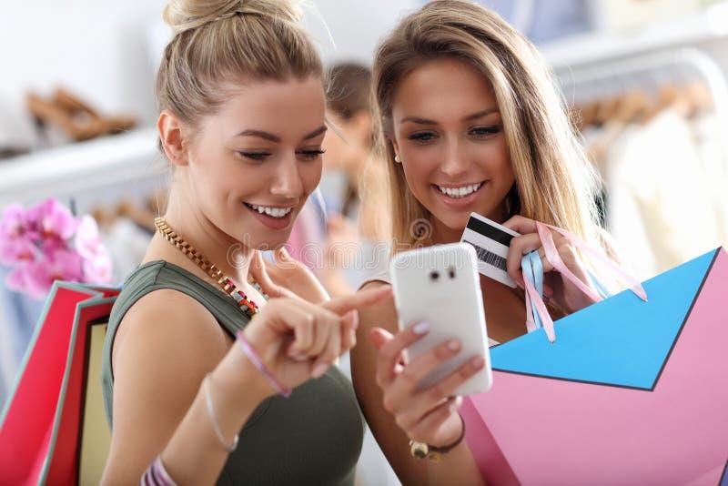 Lyckliga vänner som shoppar i lager med smartphonen fotografering för bildbyråer