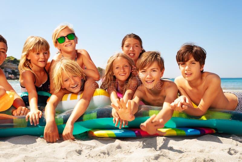 Lyckliga vänner som solbadar på den sandiga stranden i sommar arkivbild