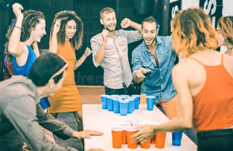 Lyckliga vänner som spelar ölpong i ungdomvandrarhem - lopp- och glädjebegrepp med fotvandrare som har kopplat från gyckel på gäs arkivfoto
