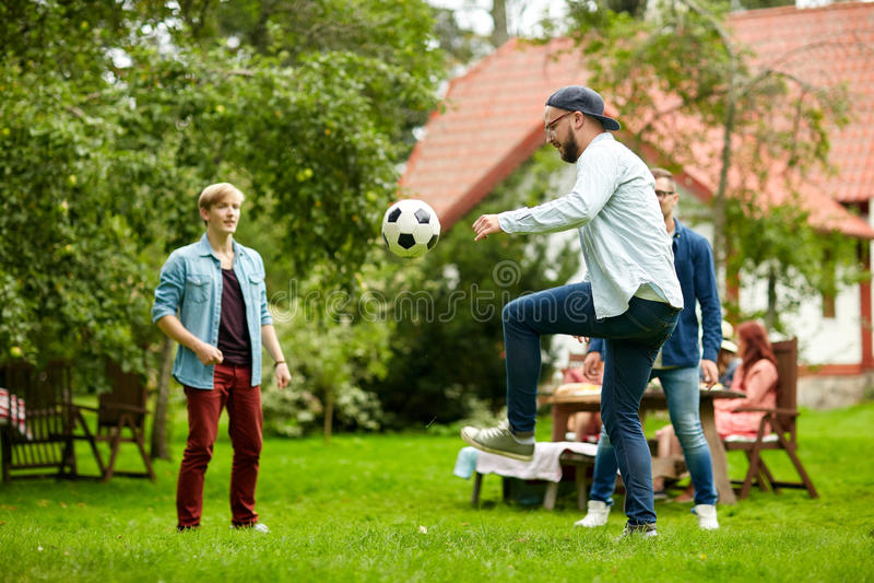 Lyckliga vänner som spelar fotboll på sommarträdgården royaltyfria foton