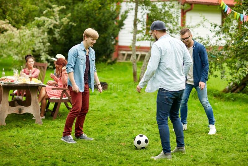 Lyckliga vänner som spelar fotboll på sommarträdgården arkivbilder