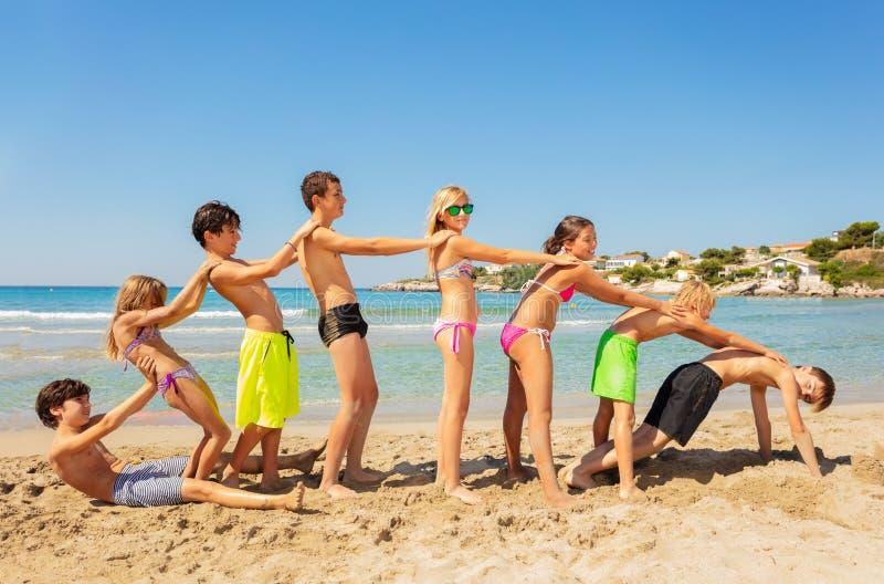 Lyckliga vänner som spelar strandlekar i sommar royaltyfria bilder