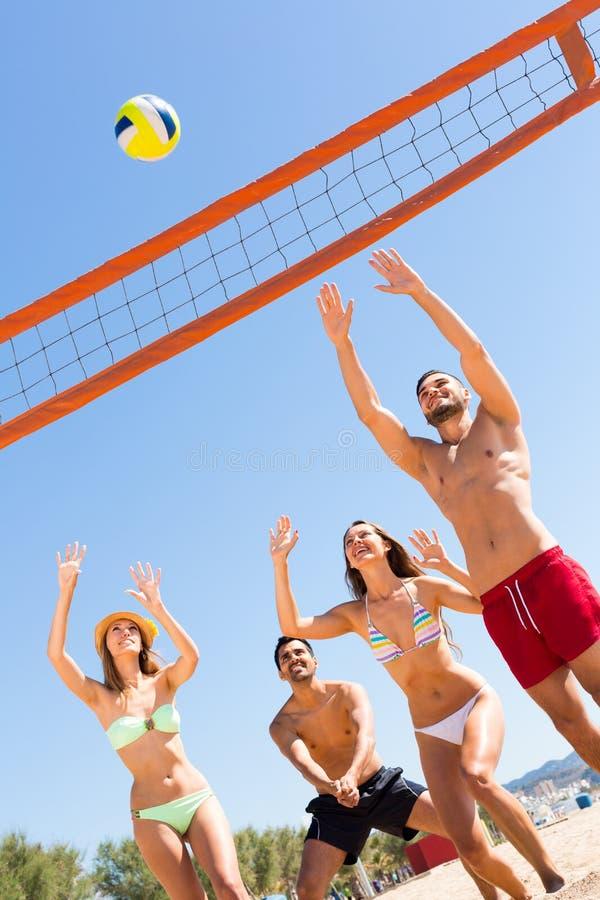 Lyckliga vänner som spelar strandsalva royaltyfria foton