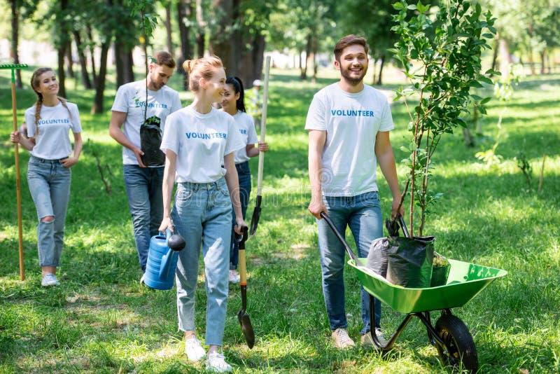 lyckliga vänner som ställa upp som frivillig och planterar träd royaltyfria foton