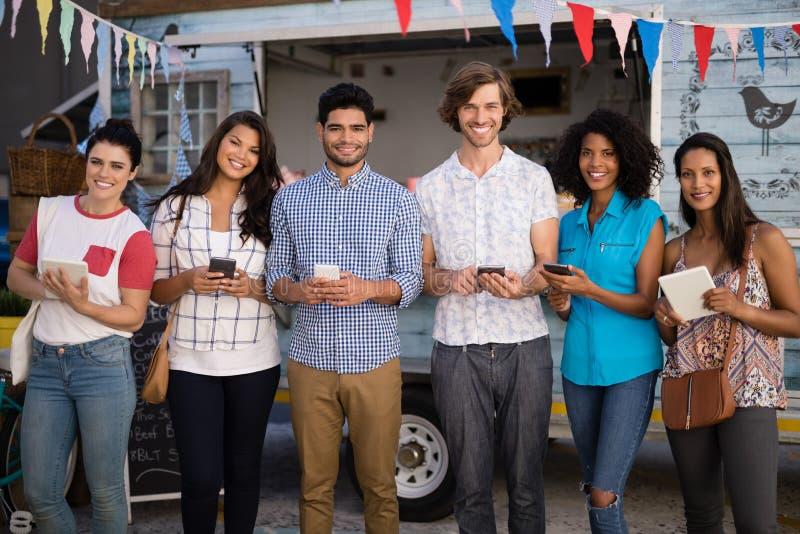 Lyckliga vänner som står med mobiltelefonen och den digitala minnestavlan royaltyfria bilder