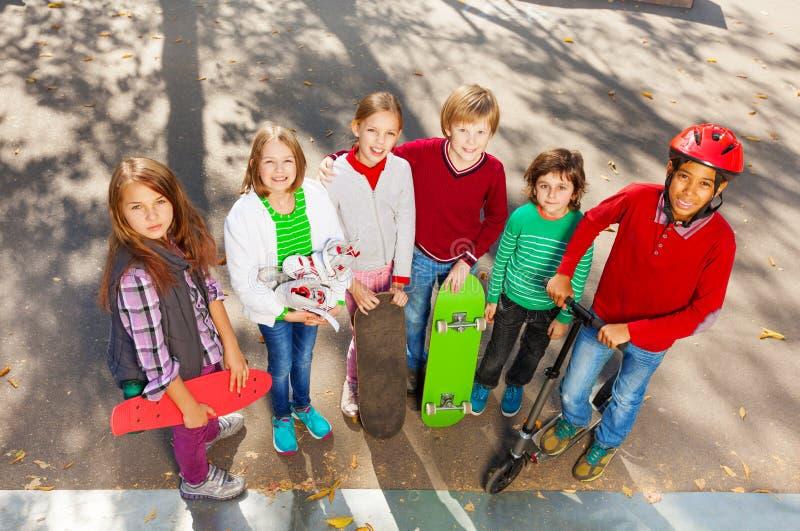 Lyckliga vänner som står nära med skateboarder fotografering för bildbyråer