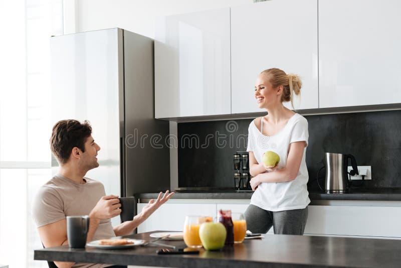 Lyckliga vänner som talar, medan sitta i kök i morgon arkivbild