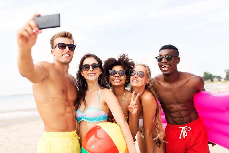 Lyckliga vänner som tar selfie på sommarstranden fotografering för bildbyråer
