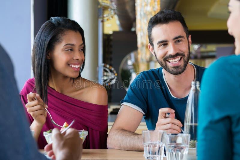 Lyckliga vänner som tillsammans äter arkivfoton