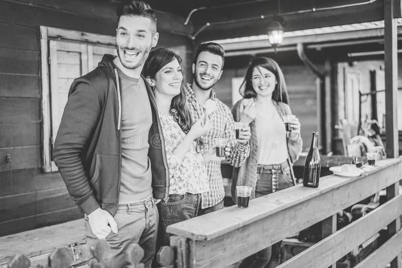 Lyckliga vänner som tycker om ett möte som dricker rött vin och tillsammans äter i trädgården - ungdomarsom har gyckel med drinka arkivfoton