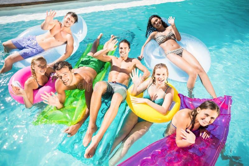 Lyckliga vänner som tycker om i simbassängen arkivbild