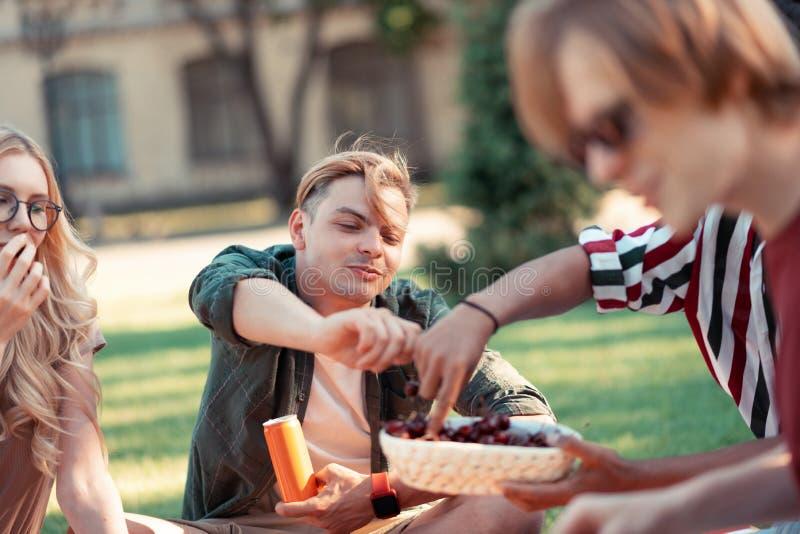 Lyckliga vänner som tycker om sommar under deras picknick royaltyfri bild