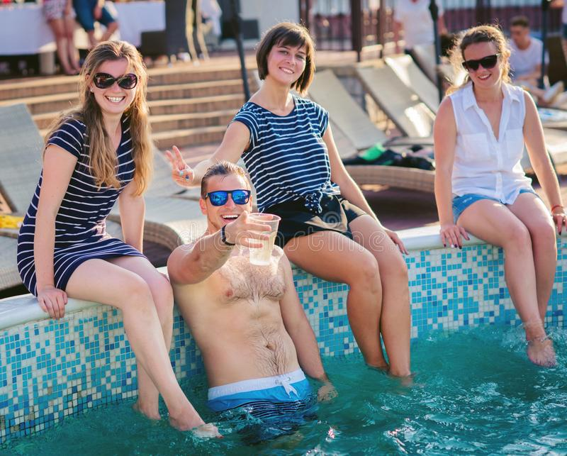 Lyckliga vänner som tycker om sommartid på simbassängpartiet royaltyfri foto