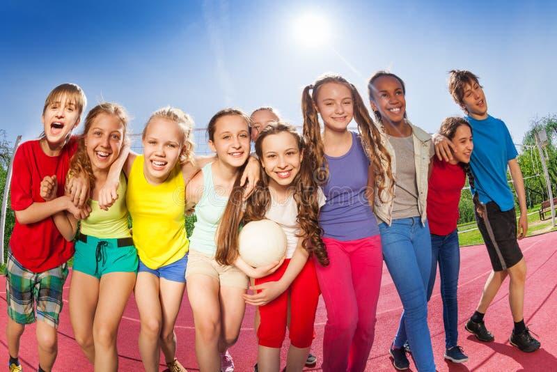 Lyckliga vänner står på domstolen för volleybollleken arkivbilder
