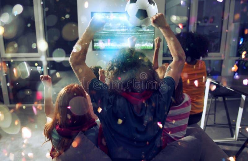 Lyckliga v?nner av fotbollsfan som h?ller ?gonen p? fotboll p? tv och firar seger med fallande konfettier dubbel exponering arkivfoton