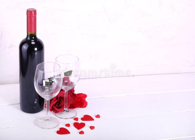 Lyckliga valentin dag med förälskade rött vin, röda rosor, vinexponeringsglas och hjärtor royaltyfri fotografi
