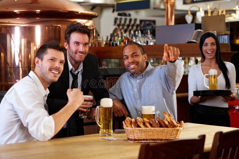Lyckliga ventilatorer som glädjande håller ögonen på TV:N i pub royaltyfri fotografi