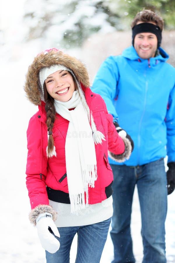 Lyckliga vinterpar i snow royaltyfria foton