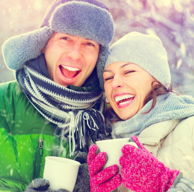 Lyckliga vinterpar med varma drinkar utomhus royaltyfria bilder