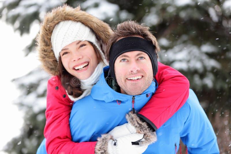 Lyckliga vinterpar på ryggen fotografering för bildbyråer