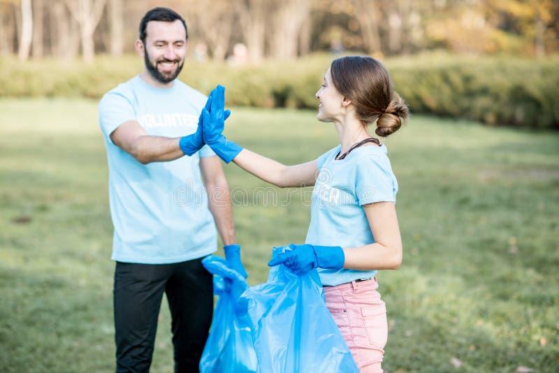Lyckliga volontärer i paarken arkivfoton