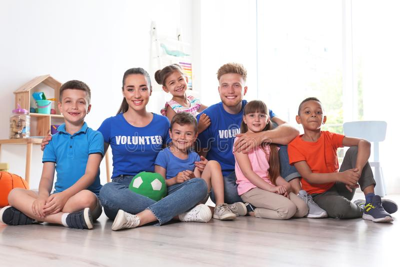 Lyckliga volontärer med barn som sitter på golv arkivbild