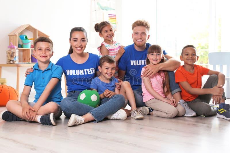 Lyckliga volontärer med barn som sitter på golv royaltyfria bilder