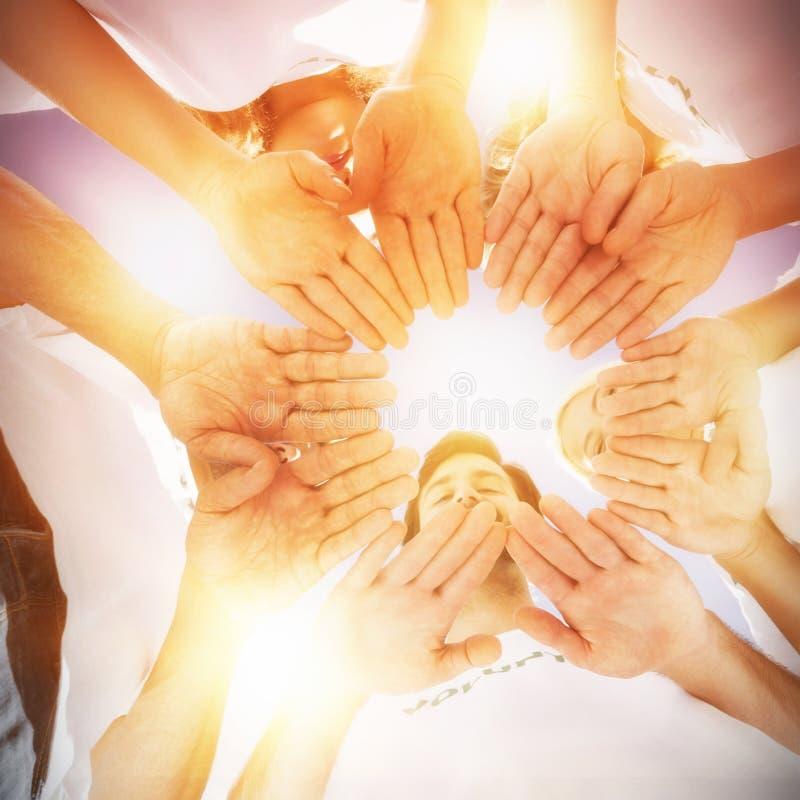 Lyckliga volontärer med händer tillsammans mot blå himmel royaltyfria bilder